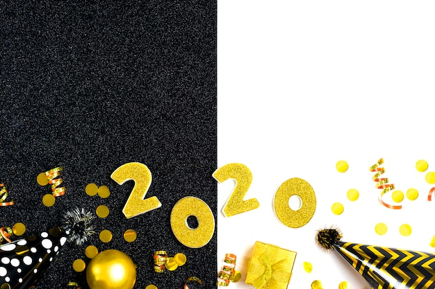 2020 zahlen mit goldenen pailletten, sternen, band, hutkappe, geschenkbox, ball auf glänzendem schwarz und weiß verziert. guten rutsch ins neue jahr, konzept der frohen weihnachten draufsicht der feiertagskarte ebenenlage
