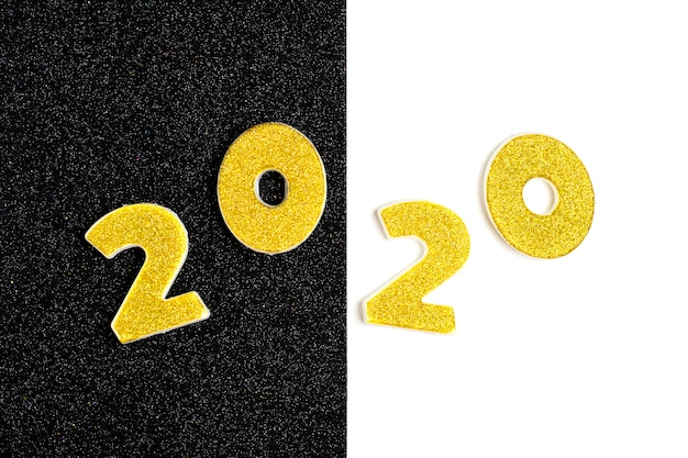 2020 zahlen mit goldenen pailletten, sternen, band, hutkappe, geschenkbox, ball auf glänzendem schwarz und weiß verziert.