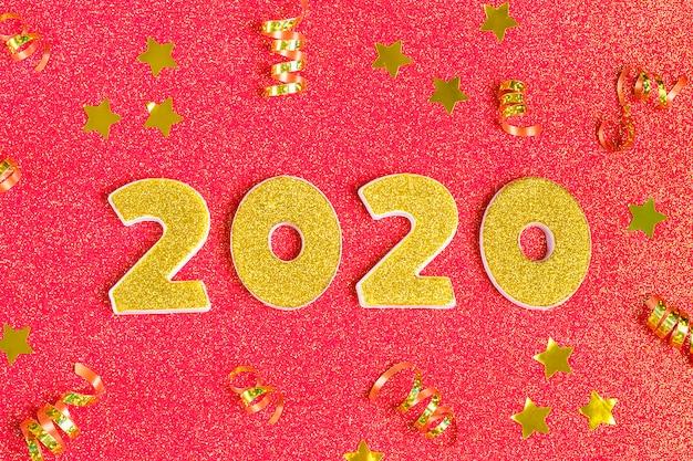 2020 zahlen mit goldenen pailletten, sternen, band, kugel auf glänzendem korallenrot verziert.