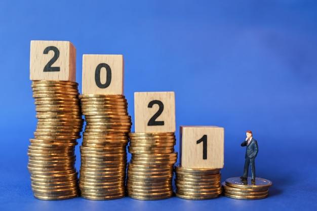 2021 geschäfts- und planungskonzept. geschäftsmann-miniaturfigurmenschen, die auf stapel von münzen mit hölzernem zahlenblockspielzeug auf blauem hintergrund stehen