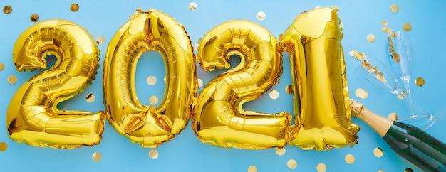 2021 goldene luftballons mit champagnerflasche und konfetti