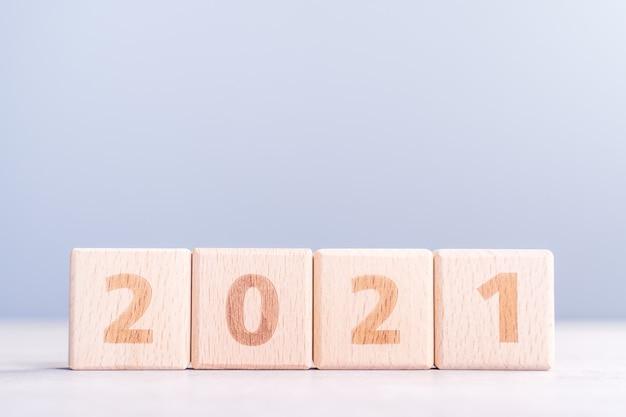 2021 neujahr abstraktes designkonzept - anzahl holzblockwürfel isoliert auf holztisch und hellem nebel blau hintergrund.