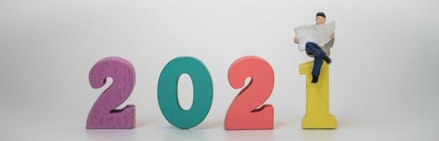 2021 neujahr, business and information cover page konzept. geschäftsmann-miniaturfigur, die sitzt und eine zeitung auf bunter hölzerner zahl auf weißem hintergrund liest.