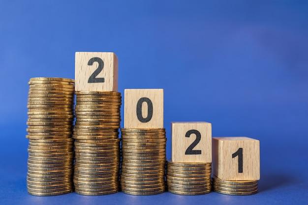 2021 neujahrsgeschäft und geldkonzept. nahaufnahme des hölzernen nummernblocks auf stapel von goldmünzen auf blauem hintergrund.