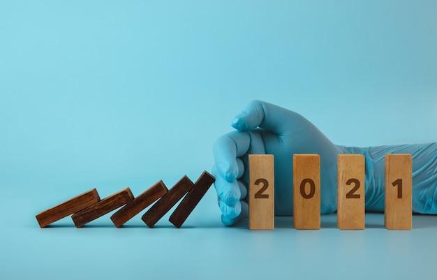2021 neujahrskonzept. hand mit medizinischem handschuh, der den dominoeffekt blockiert.