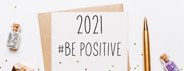 2021 positive note mit umschlag, geschenken und goldenen glitzersternen auf weiß