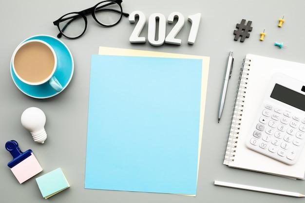2021 text mit modernem zubehör des arbeiters auf tisch, flach gelegt