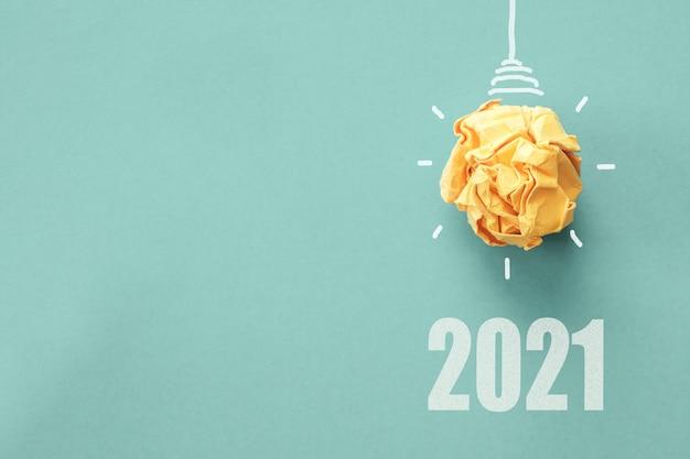 2021 und gelbe papierglühbirne auf blauer oberfläche