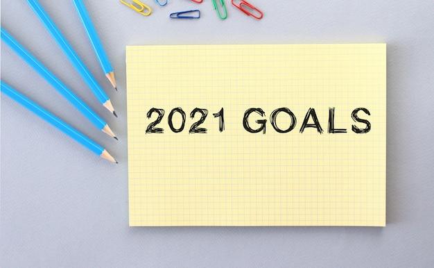 2021 ziele text im notizbuch auf grauem hintergrund neben stiften und büroklammern. konzept.