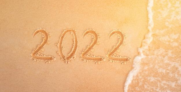 2022 figuren am sandstrand im hintergrund silvester. meereswelle wäscht die inschrift 2022 auf der gelben sandnahaufnahme weg. neujahrsferien am strand.