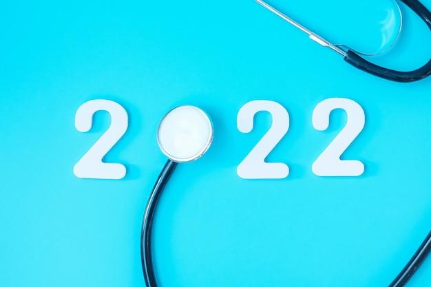 2022 frohes neues jahr für gesundheitswesen, versicherung, wellness und medizinisches konzept. stethoskop und weiße zahl auf blauem hintergrund