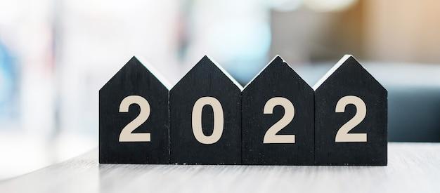2022 frohes neues jahr mit holzhausmodell im tischbüro. neue haus-, finanz-, sachversicherungs- und immobilienkonzepte