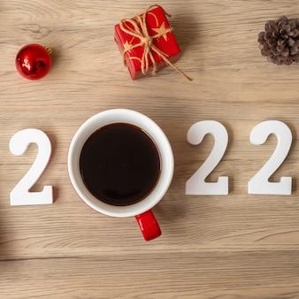 2022 frohes neues jahr mit kaffeetasse und weihnachtsdekoration auf holztischhintergrund. neuer start, lösung, countdown, ziele, plan, aktion und missionskonzept