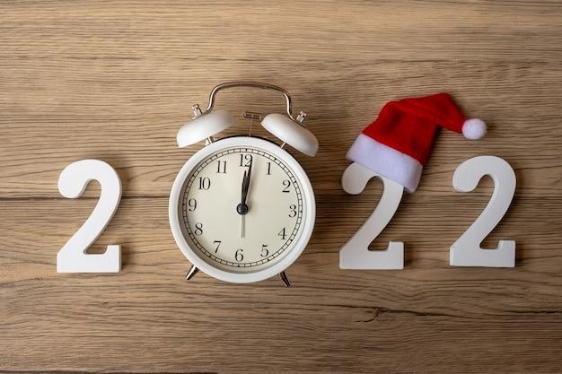 2022 frohes neues jahr mit retro-wecker und holznummer. frohe weihnachten, neuanfang, auflösung, countdown, ziele, plan, aktion und missionskonzept