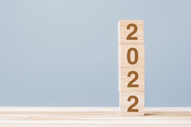 2022 hölzerne würfelblöcke auf tabellenhintergrund. lösungs-, planungs-, überprüfungs-, ziel-, start- und neujahrsferienkonzepte