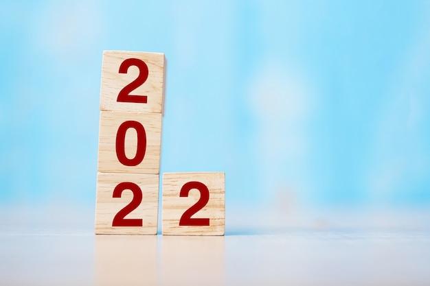 2022 hölzerner würfelblock auf tabellenhintergrund. vorsatz, strategie, lösung, ziel, geschäft und neujahr new you und urlaubskonzepte