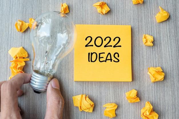 2022 ideenwörter auf gelbem zettel und zerbröckeltem papier mit geschäftsmann, der glühbirne auf holztischhintergrund hält. neues jahr neubeginn kreativ, innovation, vorstellungskraft, auflösung und zielkonzept