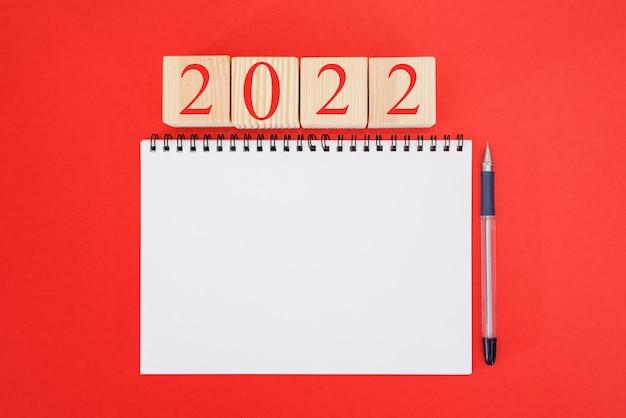 2022 mockup-notizbuch auf rotem hintergrund. neujahr. pläne für 2022, platz für text im notizblock, kalendermodell