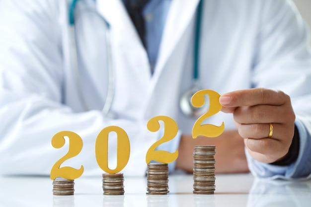 2022 neues jahr spart geld und gesundheitsplanungskonzeptarzthände setzen goldene holznummer 2022