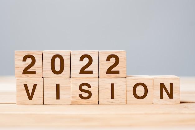 2022 vision-würfelblock auf tabellenhintergrund. lösungs-, planungs-, überprüfungs-, ziel-, start- und neujahrsferienkonzepte