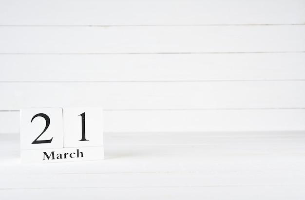 21. märz, tag 21 des monats, geburtstag, jahrestag, holzblockkalender auf weißem hölzernem hintergrund mit kopienraum für text.
