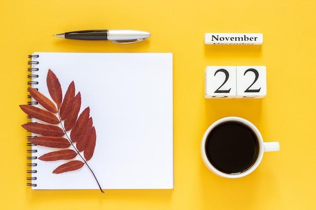 22. november tasse kaffee, notizblock mit stift und trockenes blatt