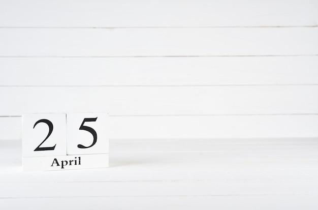 25. april, tag 25 des monats, geburtstag, jahrestag, holzblockkalender auf weißem hölzernem hintergrund mit kopienraum für text.