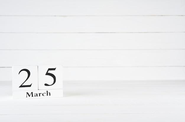 25. märz, tag 25 des monats, geburtstag, jahrestag, holzblockkalender auf weißem hölzernem hintergrund mit kopienraum für text.