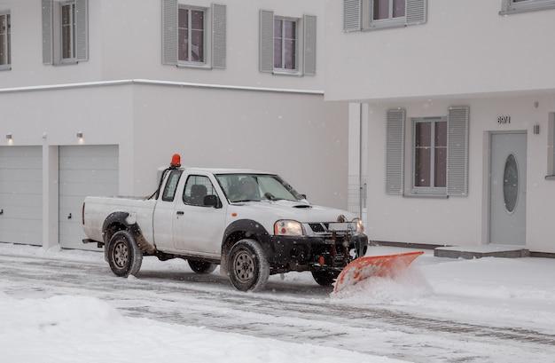 26.01.2021. piaseczno. polen. ein mit einem pflug ausgestatteter kleintransporter entfernt im winter schnee von einer geneigten auffahrt.