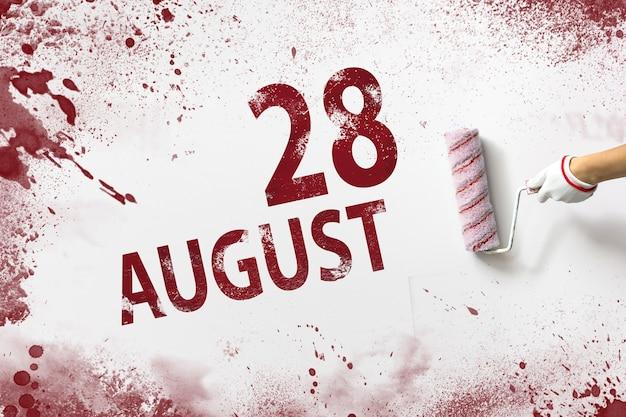 28. august. tag 28 des monats, kalenderdatum. die hand hält eine rolle mit roter farbe und schreibt ein kalenderdatum auf einen weißen hintergrund. sommermonat, tag des jahreskonzepts.