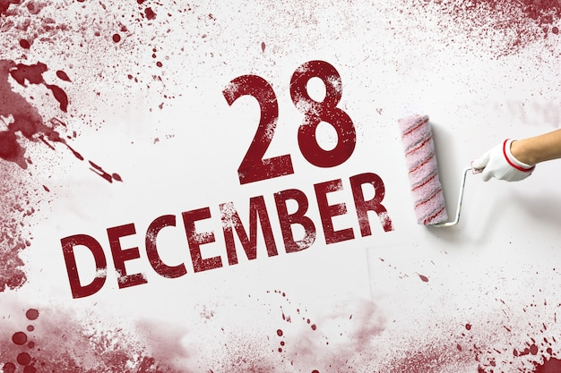 28. dezember. tag 28 des monats, kalenderdatum. die hand hält eine rolle mit roter farbe und schreibt ein kalenderdatum auf einen weißen hintergrund. wintermonat, tag des jahreskonzepts.