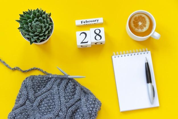 28. februar tasse tee mit zitrone, notizblock, saftigem und grauem stoff