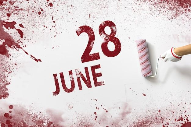 28. juni. tag 28 des monats, kalenderdatum. die hand hält eine rolle mit roter farbe und schreibt ein kalenderdatum auf einen weißen hintergrund. sommermonat, tag des jahreskonzepts.