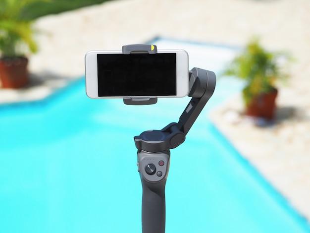 3-achsen-stabilisator der neuen generation für smartphone, handy und smartphone. schwimmbad hintergrund.