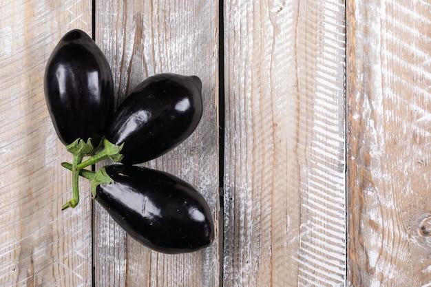 3 auberginen auf einem holz. flach liegen. platz für text