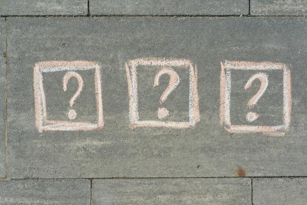 3 fragezeichen auf dem grauen bürgersteig gemalt