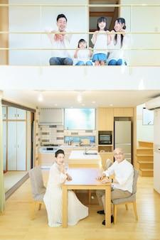 3-generationen-familie aufgereiht im 1. und 2. stock eines hauses