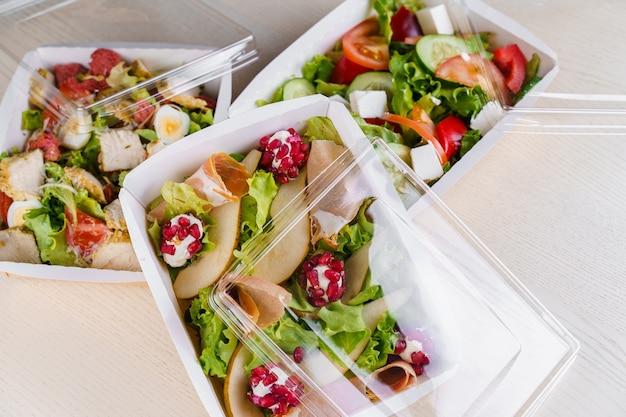 3 grüne natursalate in öko-thermobox mit microgreen, kalb, gurke, tomate, käse, granat, schale. sicherheitslieferung bei quarantäne covid 19.
