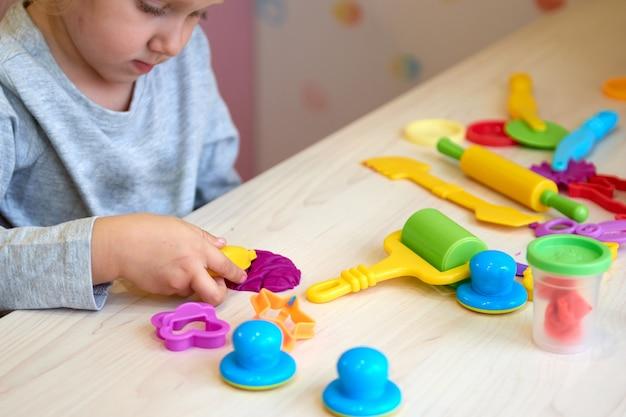 3 jahre mädchen kreative künste. kinderhände, die mit buntem tonknetmasse spielen selbstisolation covid-19, online-bildung, homeschooling. kleinkindmädchen, das zu hause lernt, zu hause lernen