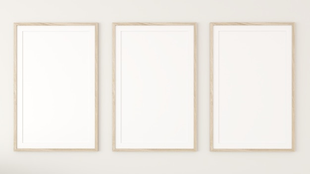 3 weiße bilderrahmen an der cremefarbenen wand