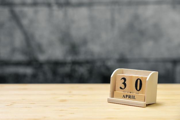 30. april hölzerner kalender auf hölzernem abstraktem hintergrund der weinlese.