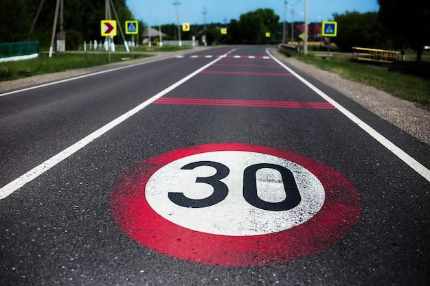 30 km / h tempolimitschild auf asphaltstraße gemalt.