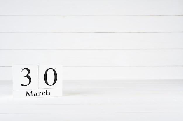 30. märz, tag 30 des monats, geburtstag, jahrestag, holzblockkalender auf weißem hölzernem hintergrund mit kopienraum für text.
