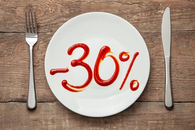 30% rabatt auf essen. verkauf von lebensmitteln. teller mit der aufschrift ketchup und gabel mit messer auf holztisch.