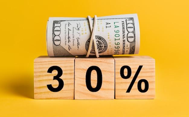 30 zinsen mit geld auf gelbem grund. das konzept von geschäft, finanzen, kredit, einkommen, ersparnissen, investitionen, austausch, steuern