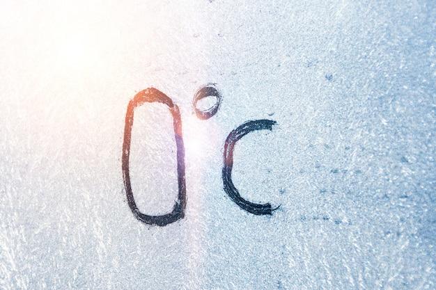 32 grad fahrenheit oder 0 grad celsius zahlenbeschriftung auf eisigem glas mit eis und frost bedeckt. das konzept des extrem kalten wetters.