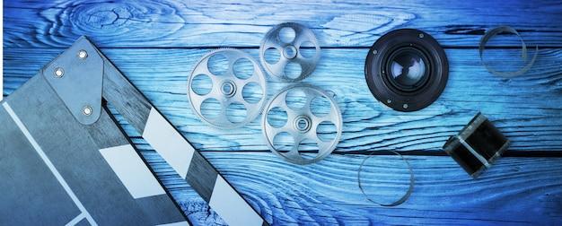 35-mm-film, spule und filmklappe mit dramatischer beleuchtung auf holzhintergrund