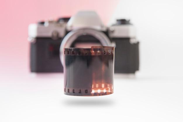 35-mm-filmrolle mit verschwommener slr-kamera