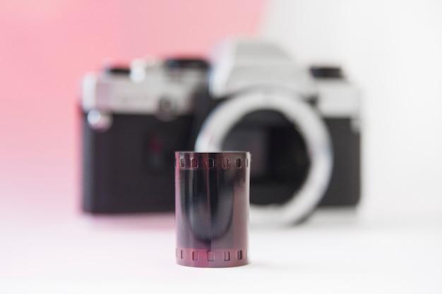 35-mm-negativfilmrolle auf einer verschwommenen slr-kamera