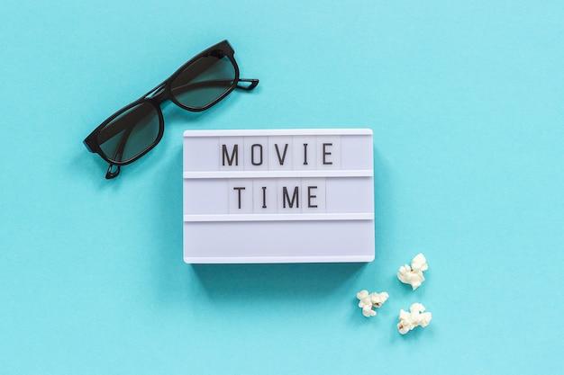 3d brille, popcorn und lightbox text filmzeit auf blauem papierhintergrund.
